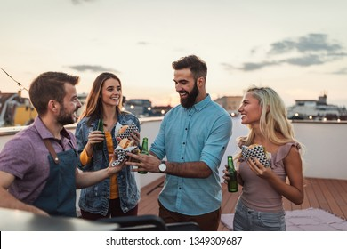 Cropped shot of four friends having fun while making barbecue on a rooftop