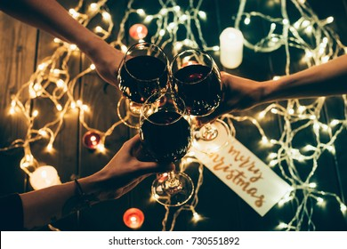 Cropped shot of four people clinking glasses with red wine over wooden table with fairylights and merry christmas card