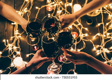 Cropped shot of four people clinking glasses with red wine over wooden table with fairylights decorations