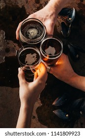 cropped shot of friends clinking mugs of beer at dark surface