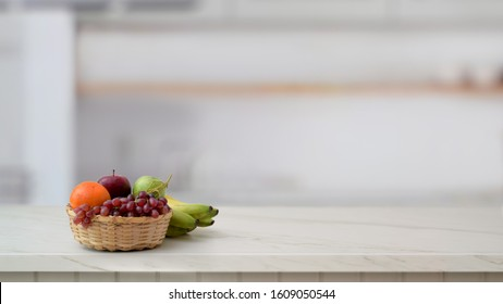 Cropped shot of fruit basket and copy space on marble desk with blurred kitchen room background