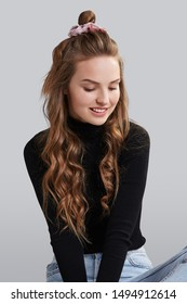 Cropped shot of a ginger girl with wavy hair, sitting on a floor. She wearing black turtleneck and blue jeans. Girl has pink hairpin on her head. Her hair is pulling in high side bun.