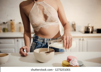 cropped shot of girl in lace bralette and jeans pouring milk into bowl with corn flakes