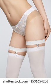 Cropped shot of a girl's low body's part. She's wearing white lace panties, white suspenders with metal clamps and white stocking. Her left hand is on a hip, she is making step.