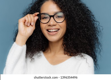 Cropped shot of good looking woman wears optical glasses, smiles broadly, shows white perfect teeth, healthy dark skin, dressed in casual jumper, isolated over blue background. Feminity concept