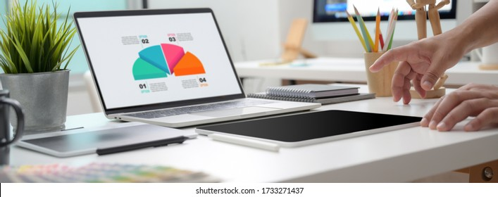 Cropped shot of graphic designer working on infographic project with drawing tablet and laptop at home office - Shutterstock ID 1733271437