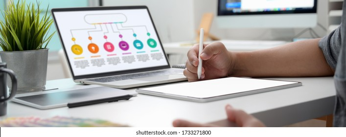Cropped shot of graphic designer working on infographic project with mock-up tablet and laptop - Shutterstock ID 1733271800
