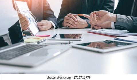 Cropped shot group of businesspeople using graph chart and computer laptop, tablet discussing about business plan together in modern office. - Shutterstock ID 1723716979