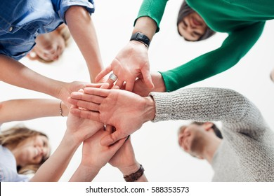 Cropped shot of a group of colleagues joining their hands together in agreement