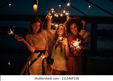 Cropped shot of a group of friends holding sparklers on a boat