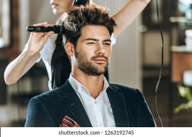 cropped shot of hairstylist combing and drying hair to handsome young man in beauty salon