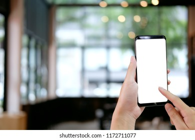 Cropped shot hands touching mockup smartphone on cafe background.