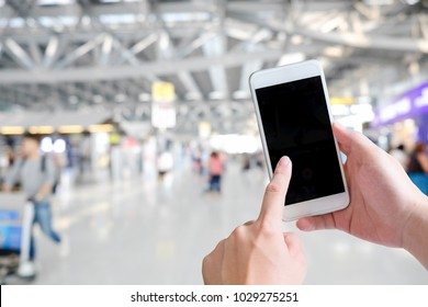 Cropped shot of hands traveler using smartphone mobile in the airport terminal