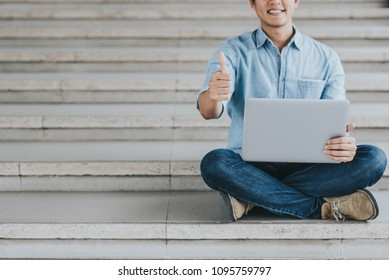 Cropped shot of happy Asian man holding laptop and showing thumb up to celebrate success or achievement