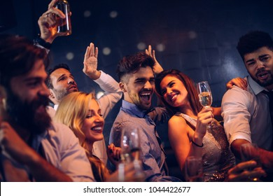 Cropped shot of an happy couple having fun with friends in the nightclub