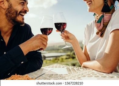 Cropped shot of a happy couple sitting at a restaurant together with a glass of red wine. Close up of a couple on a date talking and spending time with each other toasting glass of wine.
