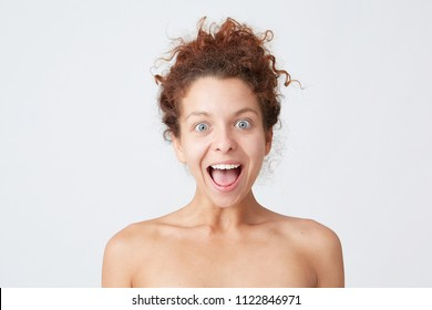 Cropped shot of happy excited curly young woman with opened mouth looking amazed and has healthy skin after applying mask or body cream, takes care of her appearance, stands half naked