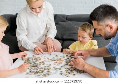 cropped shot of happy family playing with puzzle pieces at home