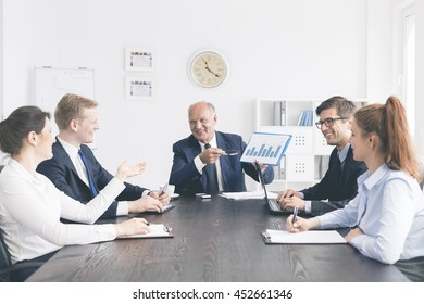 Cropped shot of a happy group of business people  in the middle of discussion, sitting at the table