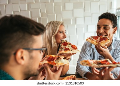 Cropped shot of a happy group of friends eating pizza