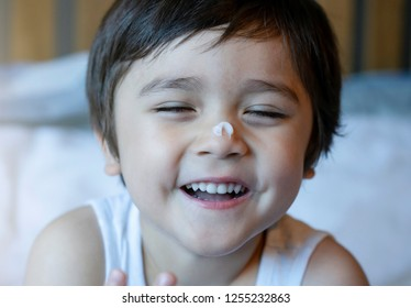 Cropped shot happy little boy applying body lotion cream on his nose after shower, Healthy Kid using cream for skincare protection,Child moisturizing his dry skin, Children problem, hygiene concept
