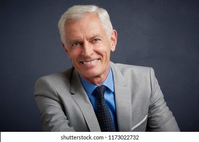 Cropped shot of happy senior businessman wearing suit while sitting at grey background.