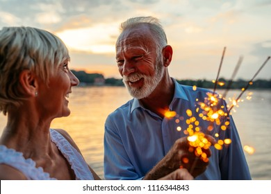Cropped shot of a happy senior couple celebrating with sparklers by the river. Warm tones.