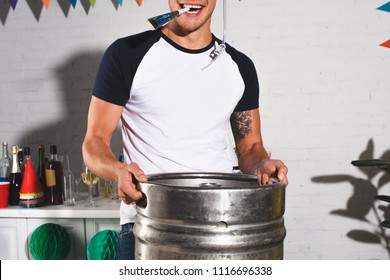 cropped shot of happy young man holding barrel of beer at home party