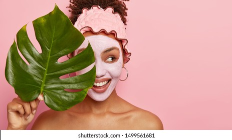 Cropped shot of happy young woman applies facial mud mask on face for removing wrinkless or fine lines, takes bath at bathroom, wears protective rosy headband, holds big plant leaf covers eyes with it