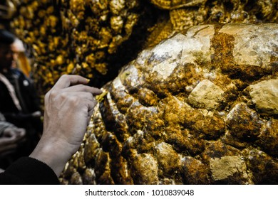 Cropped shot of human hand stick gold leaf to the body of Mahamuni Buddha statue in Mandalay, Myanmar.
