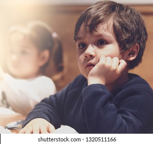 Cropped shot of Hungry boy with unhappy face waiting for food, Child with bored face sitting in restaurant in retro fliter, Unhappy kid or Spoioled children concept