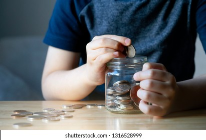 Cropped shot Kid hand putting money coins into clear jar,  Child counting his saved coins, Childhood hand holding coin, Children learning about saving for future concept