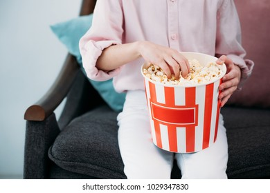 cropped shot of kid with popcorn sitting on sofa at home