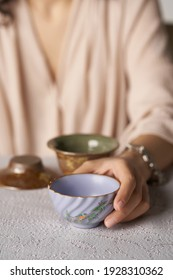 Cropped shot of lady with violet ceramic bowl with glazed surface, crazing and floral Japanese design. Woman is sitting at the table with crockery ware and holding small wavy tea bowl in her hand.