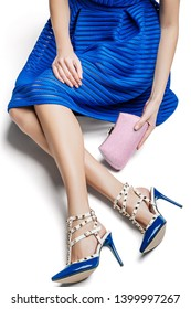 Cropped shot of lady, wearing royal blue dress and heeled slingbacks, adorned with studs. The girl is sitting on white floor, crossing her legs, holding pale pink clutch with golden clasp fastener.