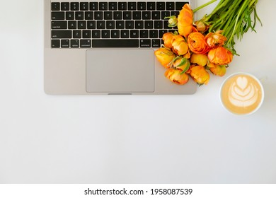 Cropped shot or laptop computer keyboard, cup of cappuccino with foam art and the bouquet of yellow-orange ranunculus flowers with a lot of copy space for text on textured table. Close up, top view.