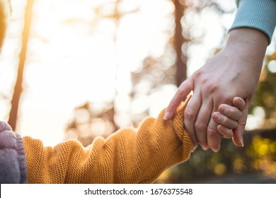 Cropped shot of a little boy holding an unrecognizable woman's hand in the park. Mother holding her little boys hand walking down the street. Mother and her son.