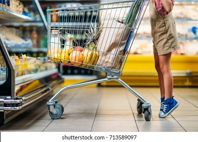 cropped shot of little child standing near shopping cart at grocery shop