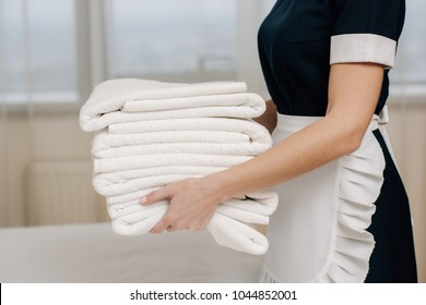 cropped shot of maid in uniform holding stack of clean towels in hotel suite