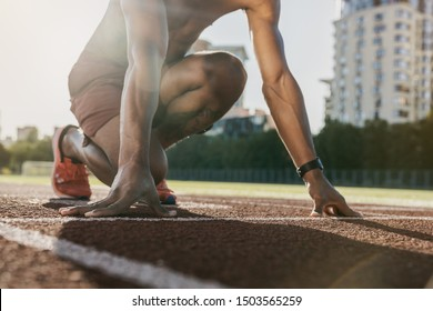 Cropped shot of male african sprinter about to start a race at stadium