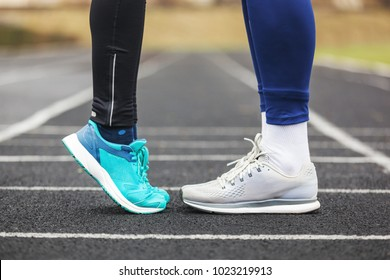 Cropped shot of a male and female legs in running shoes standing close to each other. Love concept image.
