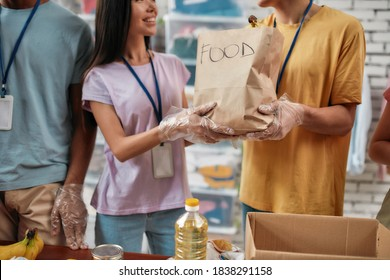 Cropped shot of male and female volunteers holding paper bag with food while packing donation for needy people, Young team working in charitable foundation, Selective focus on hands in gloves