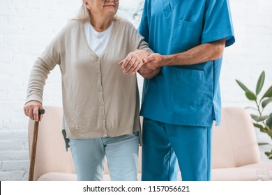 cropped shot of male nurse supporting senior woman with walking cane