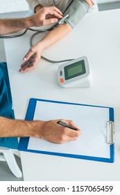 cropped shot of male nurse writing on clipboard while measuring blood pressure to senior woman