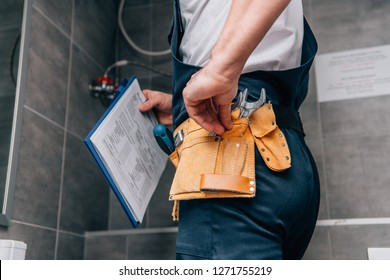 cropped shot of male plumber with clipboard and toolbelt standing in bathroom