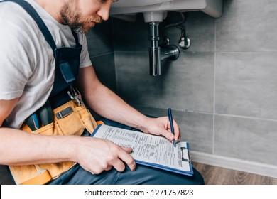 cropped shot of male plumber with toolbelt writing in clipboard near broken sink in bathroom