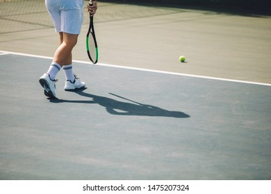Cropped shot of male tennis player walking towards the ball on hardcourt. Man in white sportswear playing tennis on hard court.