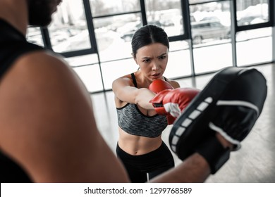 cropped shot of male trainer exercising with young sportswoman in boxing gloves at gym