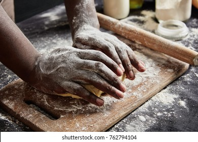 Cropped shot of male`s hands knead dough for preparing roll or pizza, works with rolling pin, uses flour and other ingridients to make pastry soft. Talented cook shows master class of baking cake