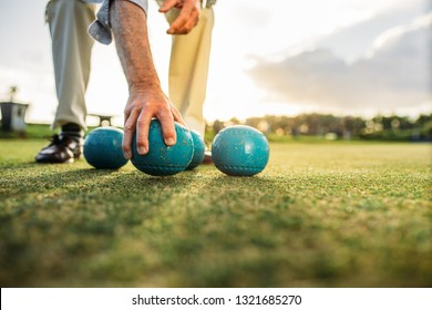 Cropped shot of a man bending down to pick a boules standing in a playground. Close up of boules lying in the lawn with a man picking one up.